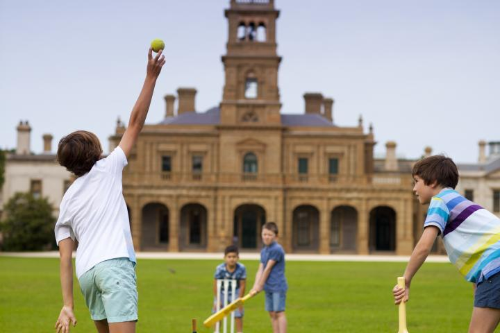 Boys playing Cricket at Werribee Park in front of Mansion